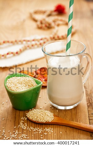Sesame seed milk in a glass. White sesame seeds. Vertical shot. - stock photo