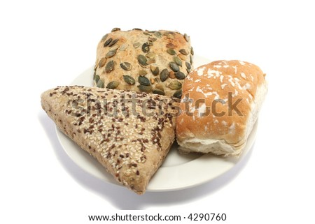 sesame seeded, pumpkin seed and plain white bread rolls on a plate - stock photo