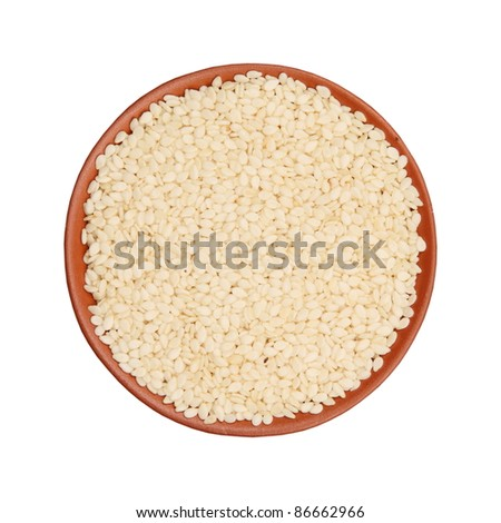 sesame seeds in a clay cup, isolated on white background