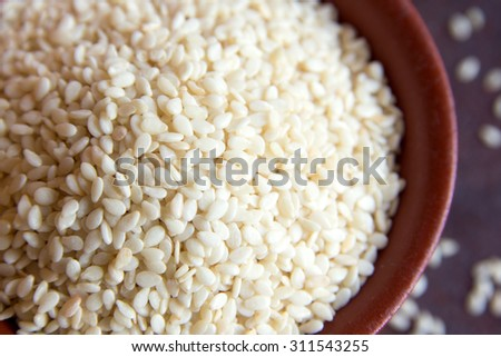 Sesame seeds in bowl close up, top view