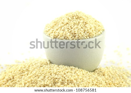 sesame seeds in bowl on white background - stock photo