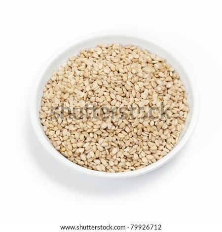 sesame seeds in porcelain bowl on white background - stock photo
