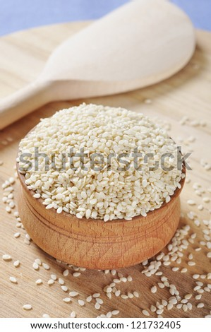 Sesame seeds in wooden bowl closeup. - stock photo