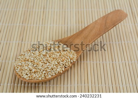 Sesame seeds on wooden spoon - stock photo
