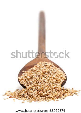 Sesame seeds on wooden spoon over white background - stock photo