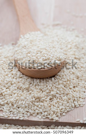 Sesame seeds with wooden spoon as close up.