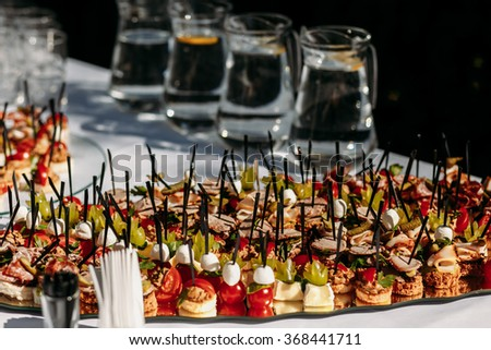 Set a variety of  canapes and snacks on a table at the restaurant to celebrate the wedding or other solemn event. - stock photo