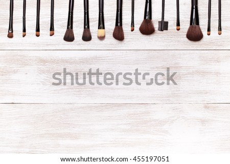 Set brushes for makeup on wooden background top view.  - stock photo
