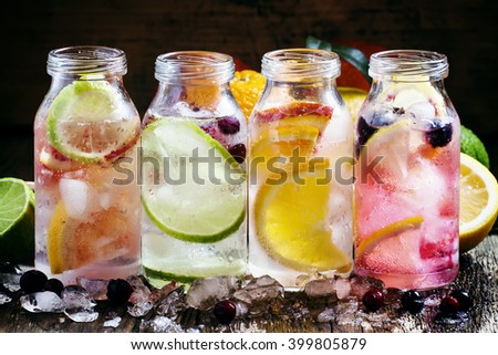 Set cold citrus lemonade: lemon with black currant, orange, lime and cranberry, grapefruit and bloody orange with crushed ice in a small bottle, selective focus - stock photo