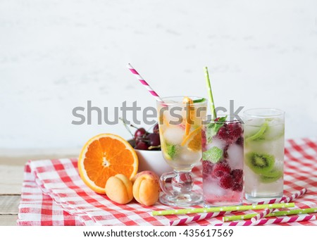 Set cold summer cocktails with strawberries, kiwi, orange and mint in steklyannmyh glasses. Fruit beverage preparation in the village tablecloths. - stock photo