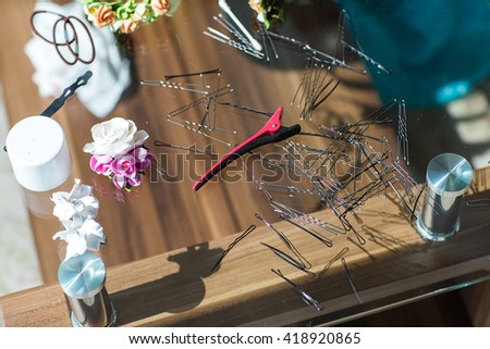 Set for a barber hairstyle: hair clips, pins, rubber bands. Accessories are on a glass table. - stock photo