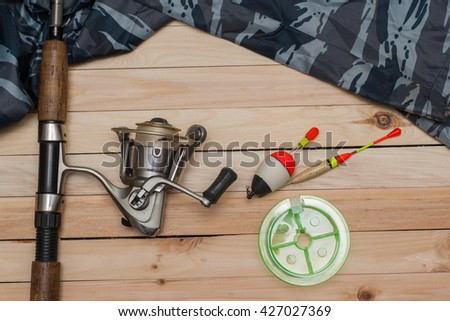 Set for fishing on the wooden background with camouflage clothing. Coil, colored floats, fishing line. Fishing. - stock photo