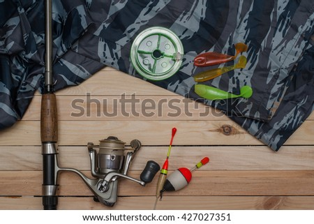 Set for fishing on the wooden background with camouflage clothing. Reel, fishing line, floats, spinning, fishing rod. Fishing and recreation. - stock photo