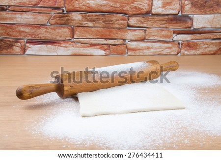 Set for home baking on a light wooden table with flour. Rolling pin and dough. - stock photo