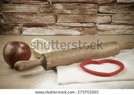 Set for home baking on a light wooden table with flour. Rolling pin, baking form, dough, half of lemon, apple. Toned. - stock photo