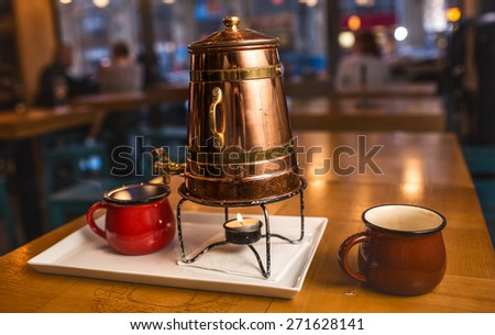Set for mulled wine. Two metal cups and teapot standing on a table - stock photo