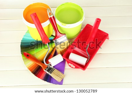 Set for painting: paint pots, brushes, paint-roller on white wooden table