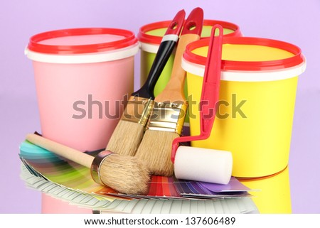 Set for painting: paint pots, brushes, paint-roller, palette of colors on lilac background - stock photo