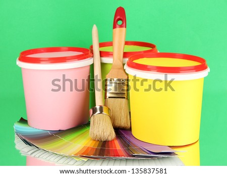 Set for painting: paint pots, brushes, palette of colors on green background - stock photo