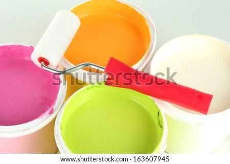 Set for painting: paint pots, paint-roller close up - stock photo