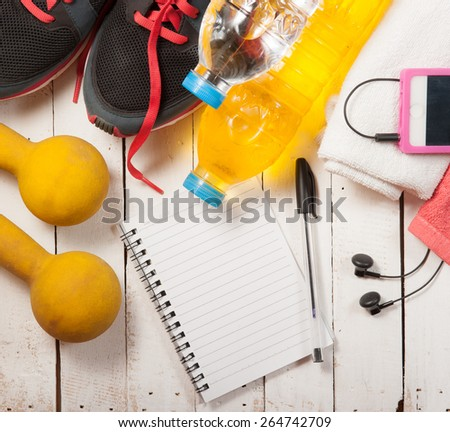 Set for sports activities and notebook on white wooden background - stock photo