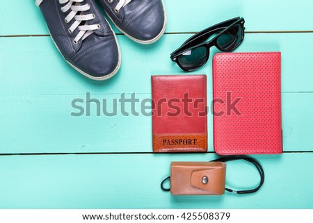 set for traveling, passport, e-book, sneakers, sunglasses, camera. on a wooden turquoise surface, a top view - stock photo