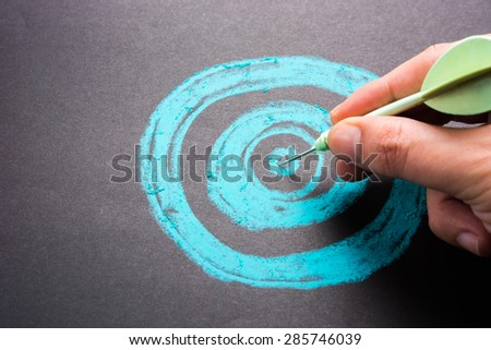 Set goal or accurate planning, hand take a dart into the center of sketching dartboard - stock photo