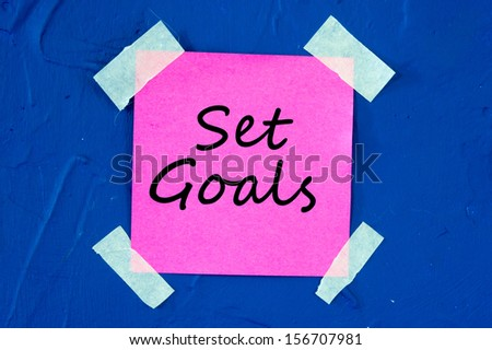 Set Goals on pink sticky paper sticked on blue wall - stock photo