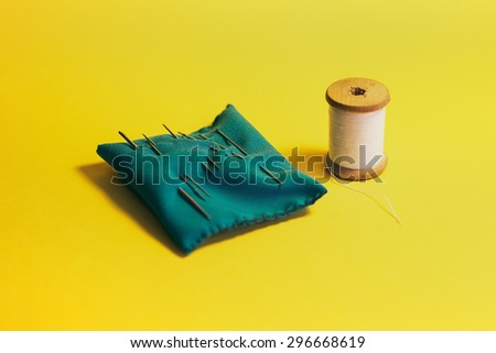 Set home seamstresses, thread and needles, yellow background - stock photo