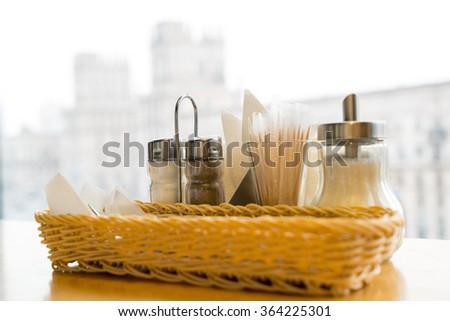 Set in cafe near Central Train Station : pepper, salt, sugar bowl, knife, fork, toothpick - stock photo