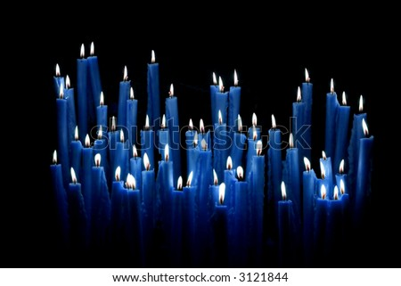 Set of a blue votive candles burning in the dark. - stock photo
