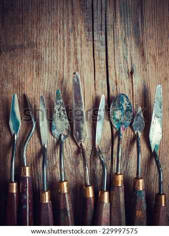 set of artist palette knifes on old wooden rustic table, retro stylized - stock photo