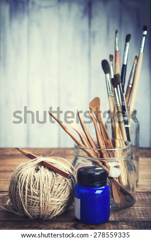Set of artist's tools with blue paint on grunge background. Toned. - stock photo