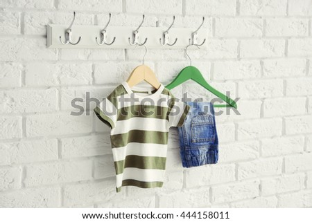 Set of baby clothes on brick wall background - stock photo