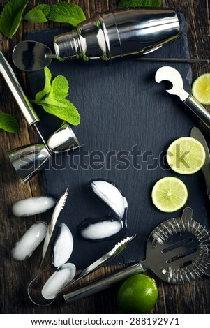 Set of bar accessories and ingredients for making a cocktails arranged on a wooden background with black board for copy space - stock photo