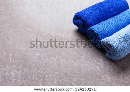 Set of bath towels on grey slate  background. Selective focus. Place for text. - stock photo