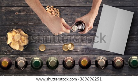 Set of beer bottles, snacks, clear menu paper and man opening bottle on wooden table, top view - stock photo
