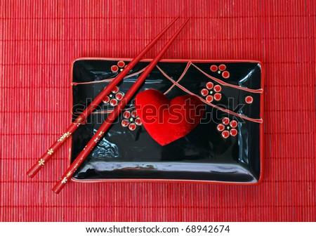 set of black chinese ceramics kitchen utensils and red heart - stock photo