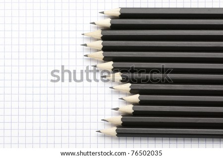 Set of black pencils on checked page. - stock photo