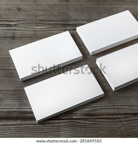 Set of blank white business cards on a dark wooden background. Template for branding identity. Shallow depth of field. - stock photo