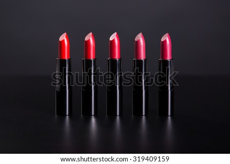 Set of bright lipsticks in shades of red color, studio shot on black background  - stock photo