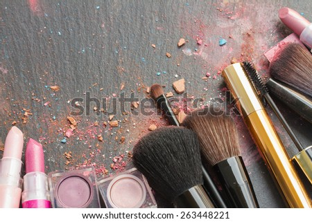 set of  brushes, lipsticks and  eye  shadows with copy space on black background - stock photo