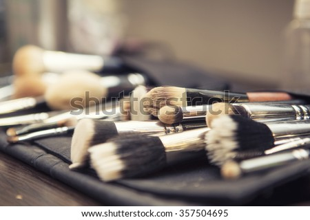 Set of brushes (make up application tools) laying on a table randomly