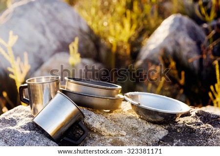 Set of camping cookware pot, bowl, pan, mug and utensils outdoor in the morning sunlight at a remote mountain wilderness campsite - stock photo