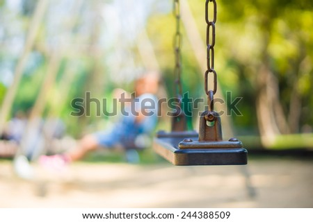 Set of chain swings on modern kids playground, kids swinging on back