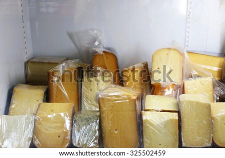 Set of cheese in plastic bags on shelf of fridge - stock photo
