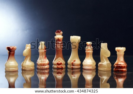 Set of chess pieces made from Onyx against dark background - stock photo