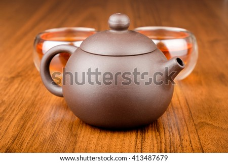 Set of chinese porcelain teapot and glass cups with tea on wooden texture desk - stock photo