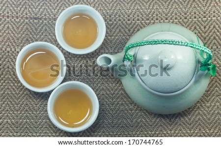 Set of chinese tea cup and tea pot on bamboo mat - stock photo