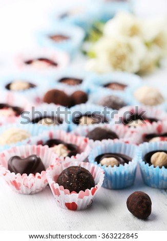 Set of chocolate candies with flowers on a light wooden background, close up